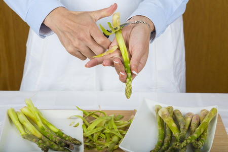 stalk: Trim and peel asparagus in the kitchen by a chef doing it with her hands and a manual peeler Stock Photo