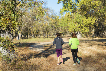 women sport: Two women doing sport and running in the forest Stock Photo