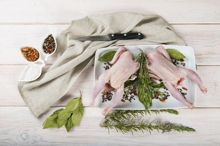 cornish: Raw poussin with herbs and spices on the table of the kitchen Stock Photo
