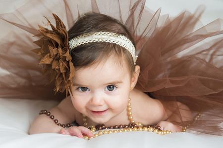 Lachende baby ballerina in bruine tutu met een parelsnoer Stockfoto