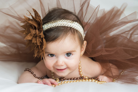 Smiling baby ballerina in brown tutu with a pearl necklace Stock Photo
