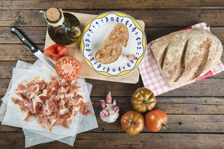 Ham with bread, tomato, garlic and olive oil to prepare the typical Spanish toast Imagens