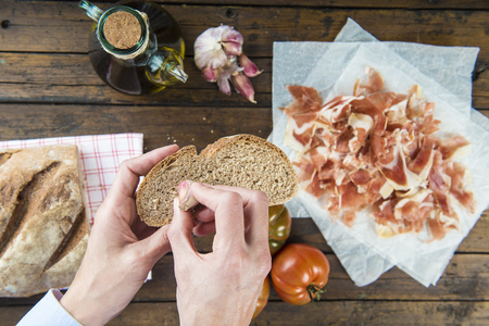 spanish style: Chef rubbing garlic on a bread slice to prepare ham with garlic, tomato bread and olive oil Spanish style