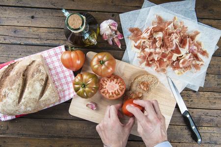 rubbing: Chef rubbing tomato on a slice of bread to prepare a spanish toast of ham, garlic and olive oil