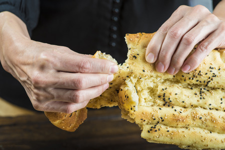 tearing: Tearing of a piece of barbari or Persian bread with hands