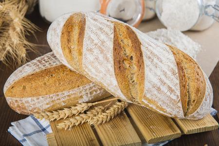 pan de masa fermentada con espigas de trigo y harina en la mesa de panadería