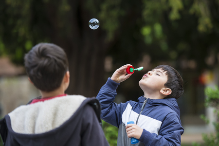 five years': Five years old child blowing soap bubbles outdoors in a garden