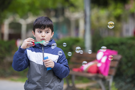 five years old: Five years old child blowing soap bubbles outdoors in a garden