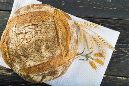 Homemade sourdouhg bread loaf decorated with burlap and cereal grains and ears