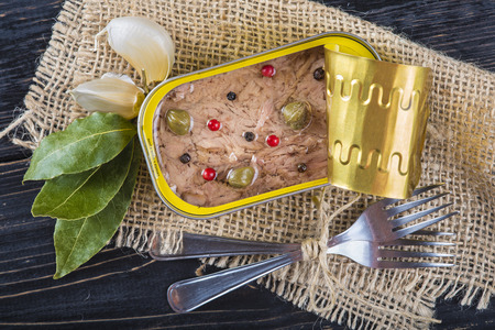 Light tuna in olive oil canned dressed with herbs and spices on a burlap and a wooden background Stock Photo