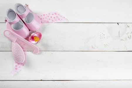 Expecting a baby background with shoes and a pacifier on a white wooden surface Stock Photo