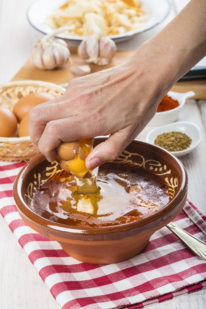 Chef cracking an egg on a Castilian or garlic soup