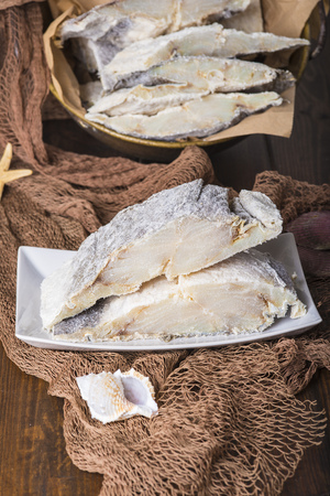 redes de pesca: Uncooked salted preserved cod cut in portions on fishing nets Foto de archivo
