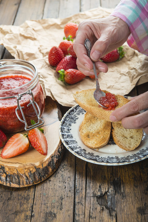 smearing: Smearing homemade strawberry jam on a toast for breakfast
