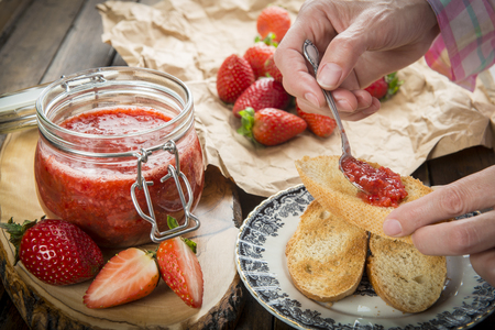 Smearing homemade strawberry jam on a toast for breakfast
