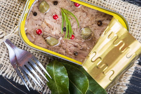 peppercorn: Light tuna in olive oil canned dressed with herbs and spices on a burlap and a wooden background Stock Photo
