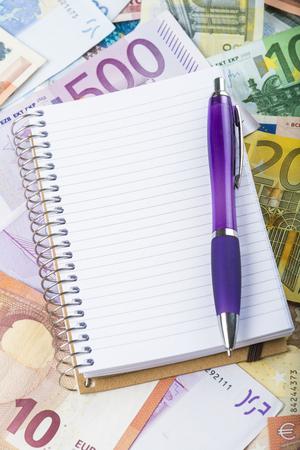 Notebook en pen op een geld achtergrond gemaakt van bankbiljetten