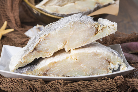 salted: Uncooked salted preserved cod cut in portions on fishing nets Stock Photo