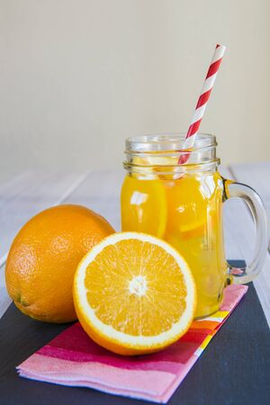 Orange juice in a glass mason jar with a stripped drinking straw