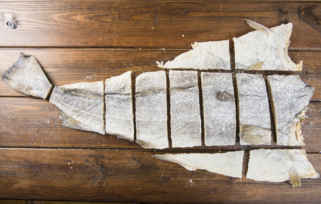 dried fish: Traditional cut of salted cod on a wooden board Stock Photo