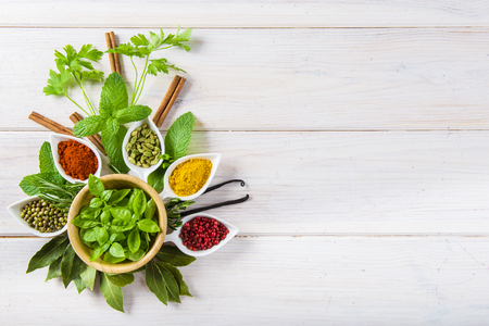 Fresh and colorful herbs and spices assortment on a white wooden background