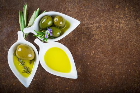 iron oxide: Extra virgin olive oil and green olives on an old iron surface with a copy space