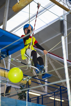 descender: children enjoying a Zip line and climbing training indoors with safety equipment Stock Photo