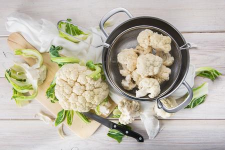 調理する台所のテーブルに原料と新鮮なカリフラワー 写真素材