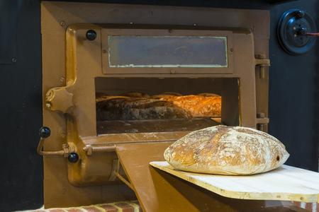 Horno de leña tradicional en una panadería y una pala de panadero con pan Foto de archivo - 88931750