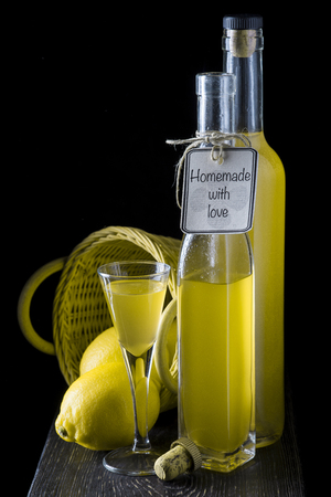 Italian limoncello in a shot glass and a bottle on a black wooden background