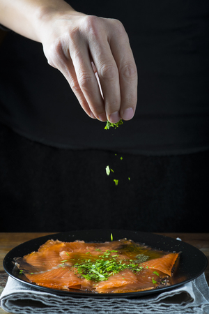 Dressing a plate of gravlax salmon with olive oil and  dill