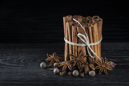Cinnamon sticks and other spices on a dark background