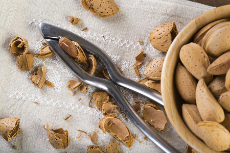 Bowl with almonds and a nutcracker on the table Stock Photo