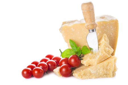 Parmesan cheese or parmigiano reggiano with cherry tomatoes and basil leaves isolated on a white background Stock Photo