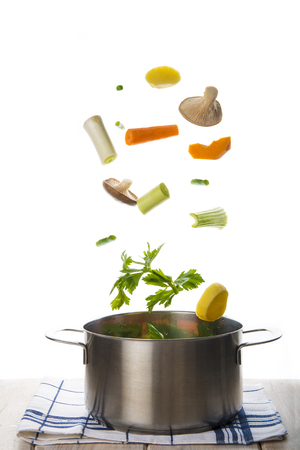 Fresh vegetables to cook a soup falling into a pot isolated on a white background Stock Photo