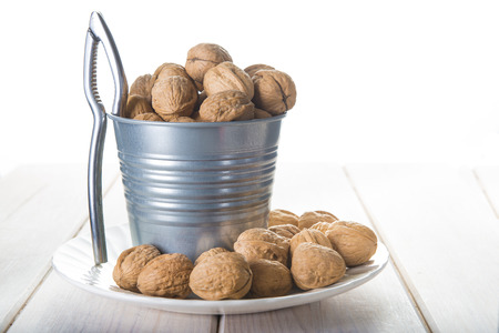 Bucket full of walnuts with a nutcracker on a wooden white background