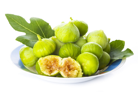 Fresh white ladys neck figs with its leaves isolated on a white background