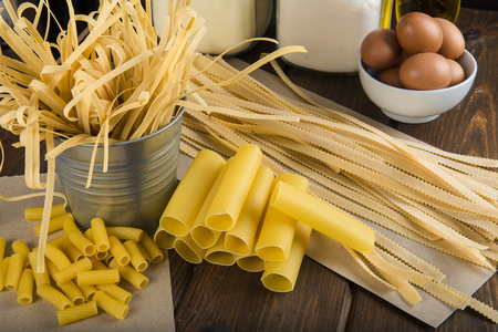 Assortment of homemade fresh egg pasta with a blackboard background