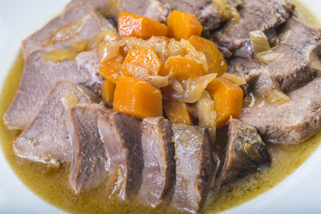 Stewed pork tongue Spanish style with onion and carrots