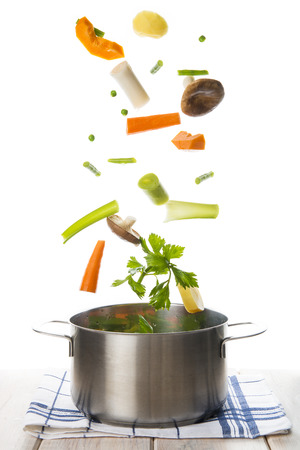 Fresh vegetables to cook a soup falling into a pot isolated on a white background Foto de archivo