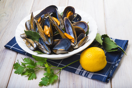 Steamed mussels with lemon and parsley on the table