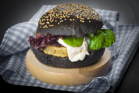 Fish burger in a black bun with sesame and poppy seeds and fresh lettuce and tomato
