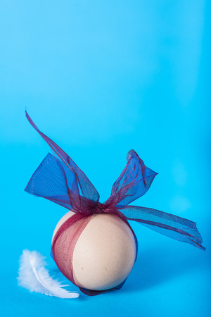 Easter egg decorated for a gift on a blue background