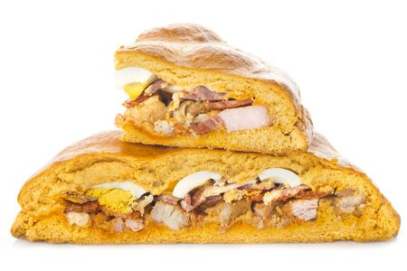 Traditional food for easter time in Spain called hornazo, a stuffed bread with pork meat and eggs isolated on a white background Фото со стока