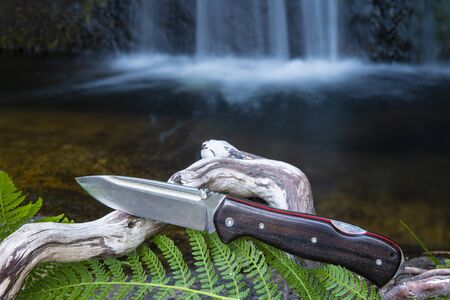 knife for bushcraft and survival in the wild near to a waterfall