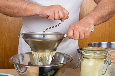 Chef mashing boiled potatoes to make gnocchi in the kitchen