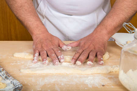 Chef preparing gnocchi on a wooden board in the kitchen