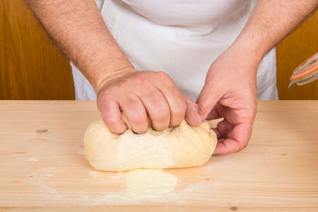 chef kneading dough to make gnocchi on a wooden table