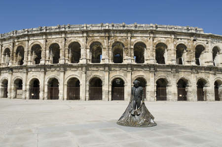 Nimes, Gard, France-April 10, 2011: Ancient arenas and a bullfighter statue Stock Photo