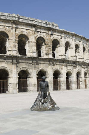 Nimes, Gard, France-April 10, 2011: Part of ancient arenas with bullfighter statue